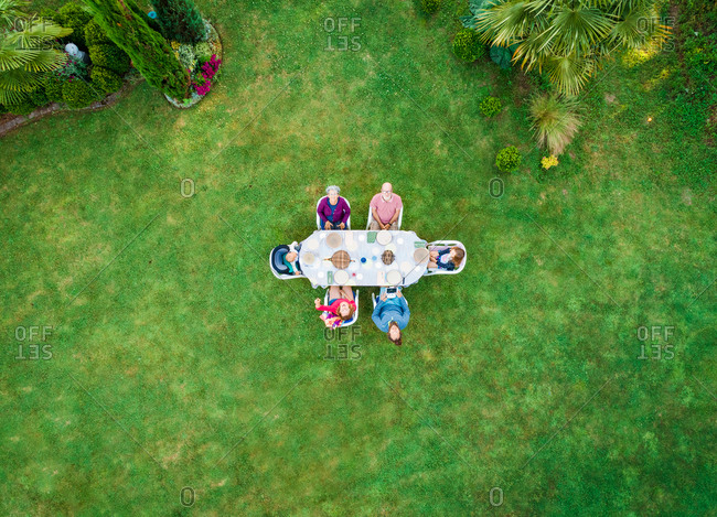 Aerial view of extended family at garden table for lunch.