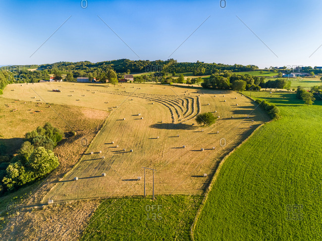 Aerial view of tractor harvesting straw bales in field in Correze, France.