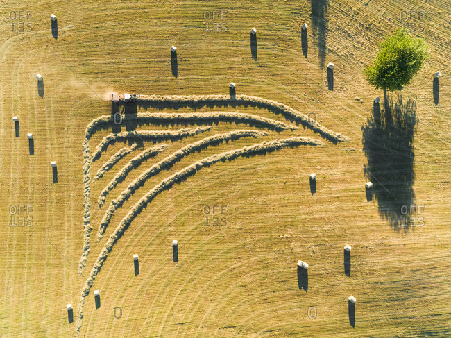 Abstract aerial view of tractor harvesting straw bales in field in Correze, France