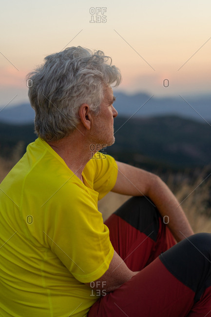 Side view of aged man looking away while sitting on Montcau mountain and resting on sunset