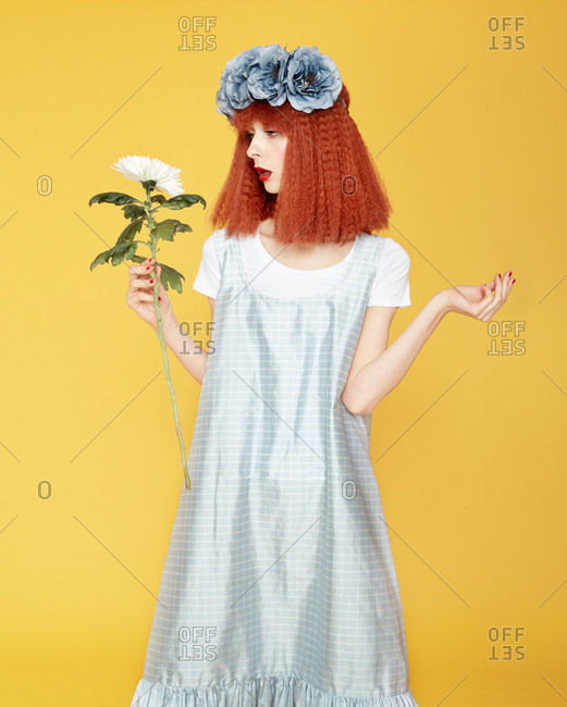 Isolated view of red haired model in blue gown and artificial flowers on head upping hands, holding and looking at chrysanthemum on yellow background