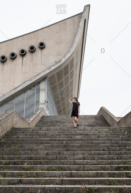 From below shot of woman in black dress walking down gray concrete stairs with modern building on background