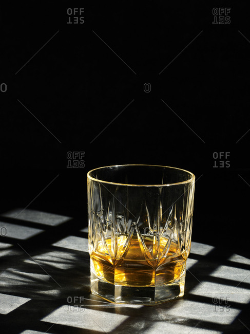 Close-up of clear crystal glass filled with golden liquor on gray background in shadow of grid