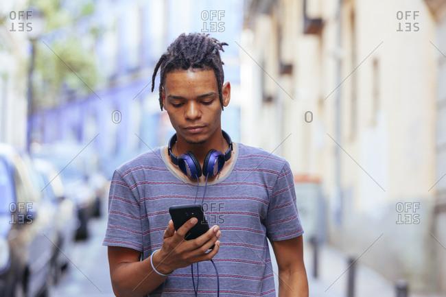 African American guy in headphones on street