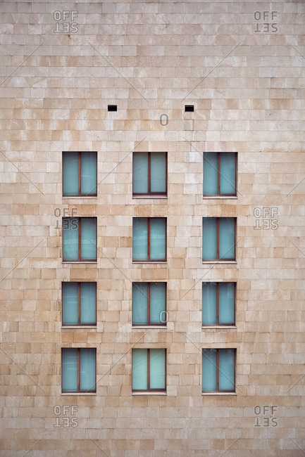 Light brown brick wall of building with little similar�closed windows in Bilbao
