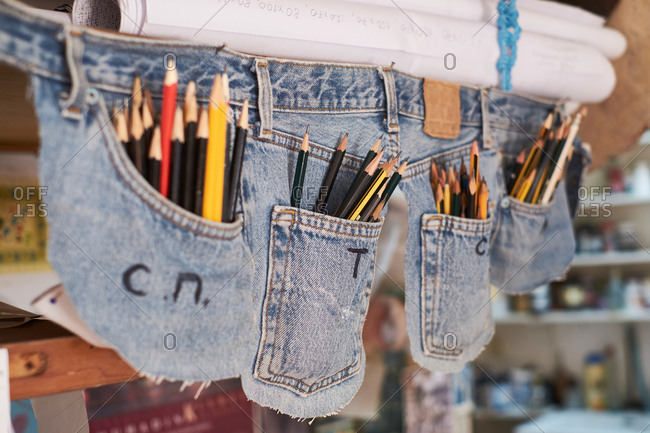 Creative pen case made of jeans pockets full of writing pencils hanging in room