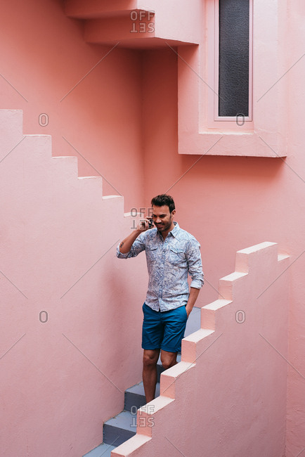 Happy man walking in a pink building stairs with a mobile phone