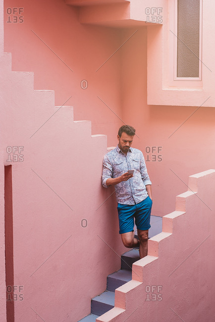 Thoughtful man leaning in a pink building stairs with a mobile phone