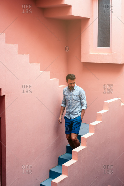 Thoughtful man walking in a pink building stairs
