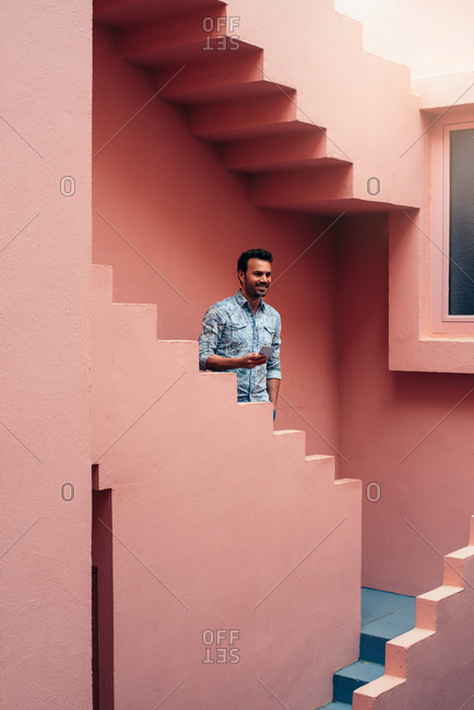 Happy man leaning in a pink building stairs with a mobile phone