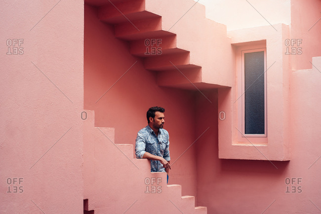 Thoughtful man leaning in a pink building stairs