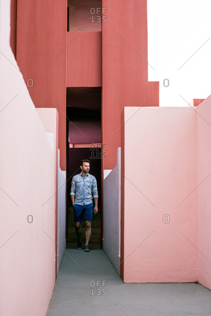 Thoughtful man walking in a pink building