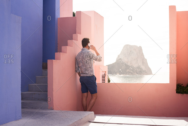 Man seating in a blue and pink building taking a photography of the landscape with a mobile phone