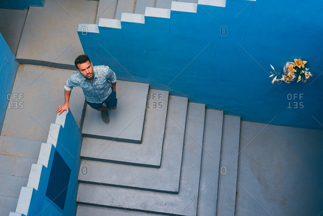 Thoughtful man leaning in a blue building stairs