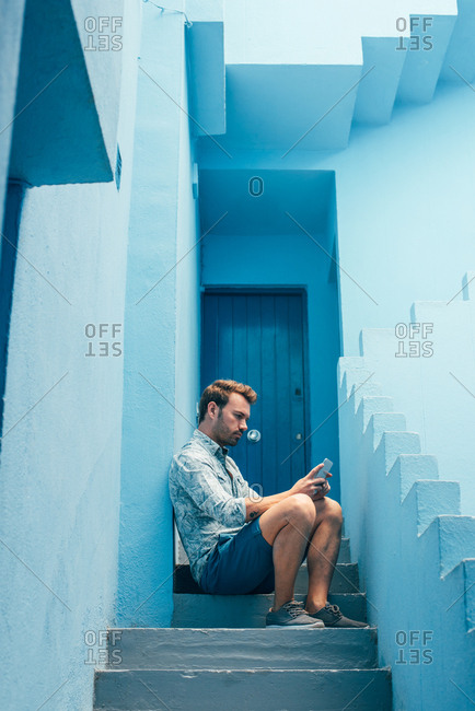 Man seating in a blue building stairs with a mobile phone