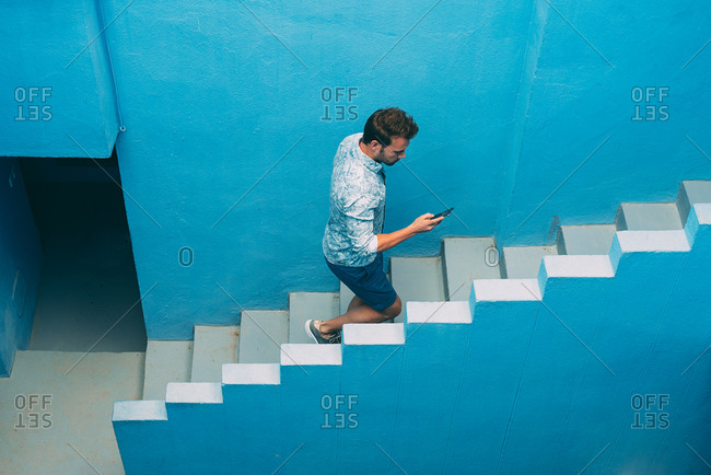 Man walking in a blue building stairs with a mobile phone