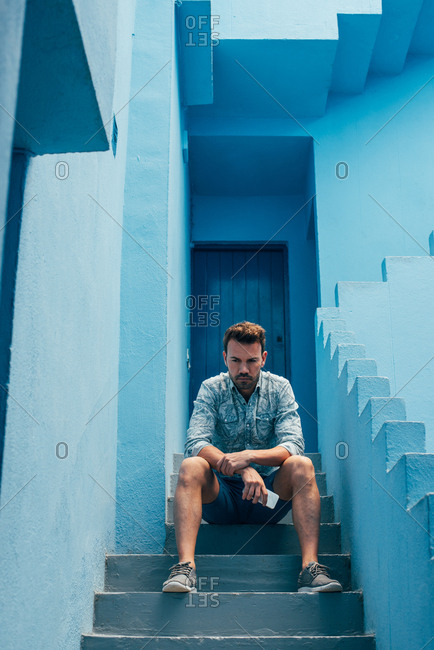 Thoughtful man seating in a blue building stairs with a mobile phone