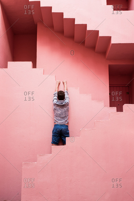 Man hanging in a pink building stairs