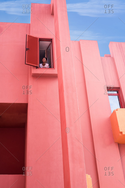 Black woman standing in a colorful geometric building windows