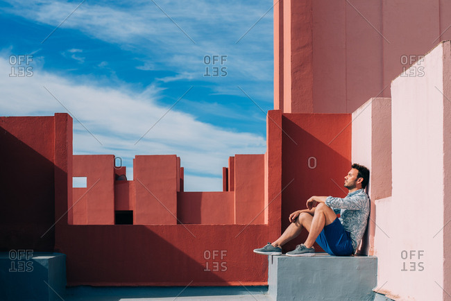 Man leaning in a colorful rooftop building