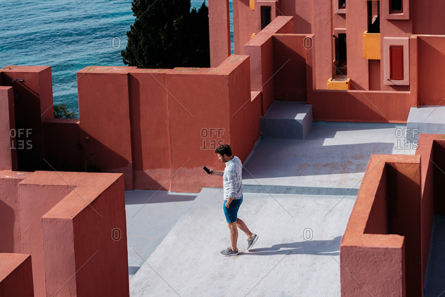 Man walking in a colorful geometric building roof terrace with mobile phone