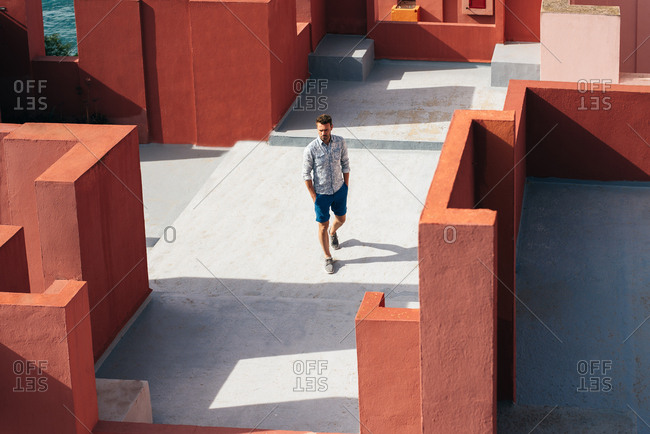 Man walking in a colorful geometric building roof terrace