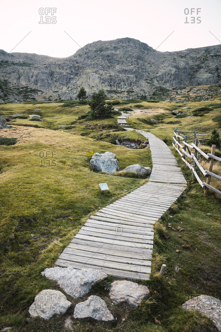 Perspective view of wooden walkway on rocky green terrain with mountains on background, Spain