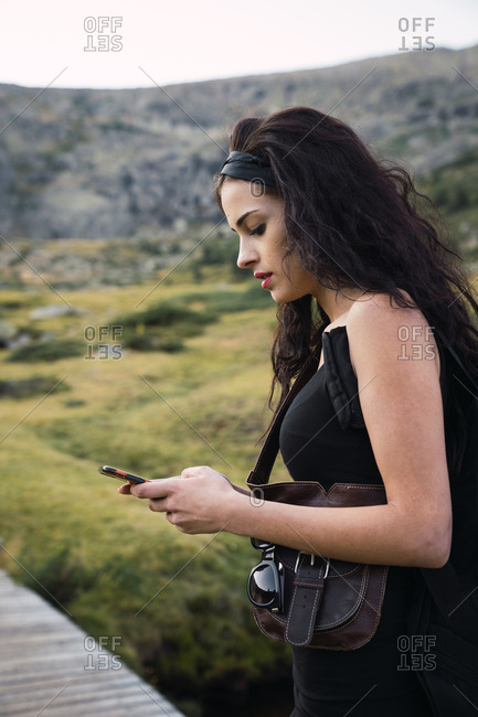 Side view of beautiful brunette with backpack standing on walkway in green mountains and using phone
