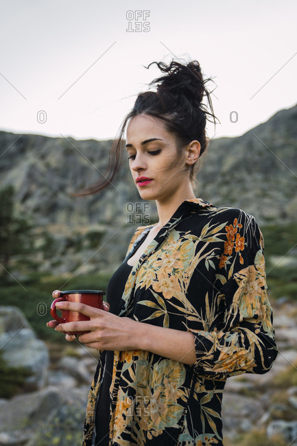 Woman standing with coffee on stone