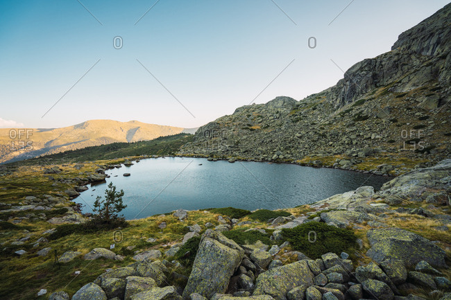 Beautiful small lake among rocks and green stones in mountain valley of Guadarrama, Spain