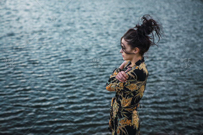 Side view of woman in colorful shirt embracing herself and looking away standing on background of blue water in ripple