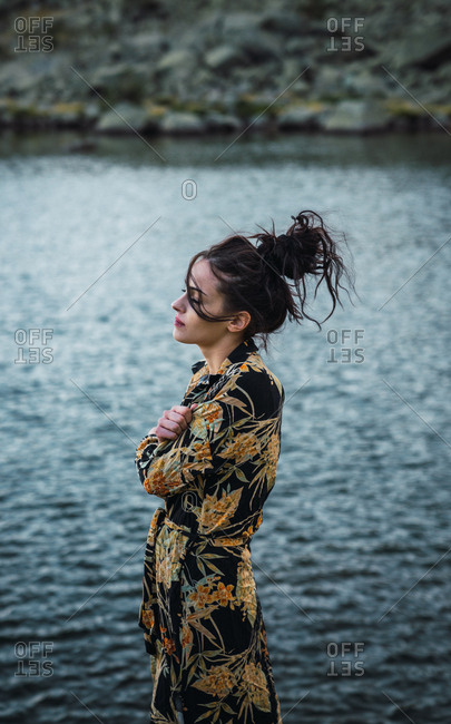 Young woman standing alone on shore