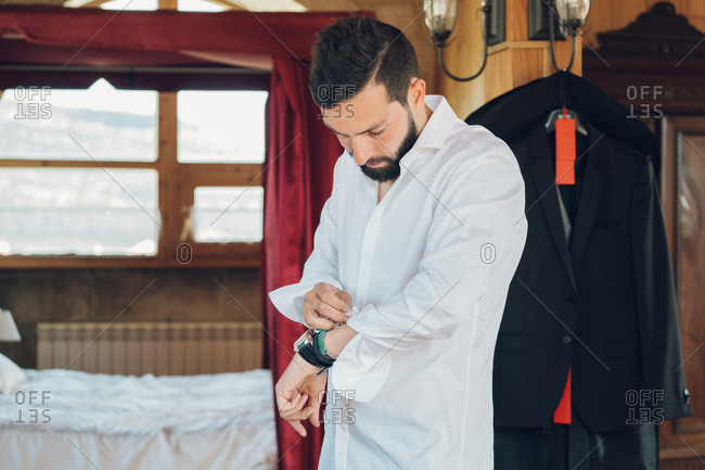 Young handsome man with dark hair and beard putting on white shirt in bedroom with new black costume hanging on clothes hanger