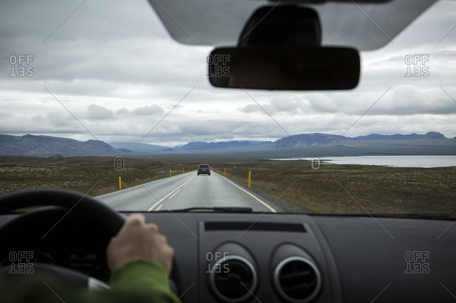 Crop view of person's hand driving automobile on road passing between water, dale and hills in Iceland
