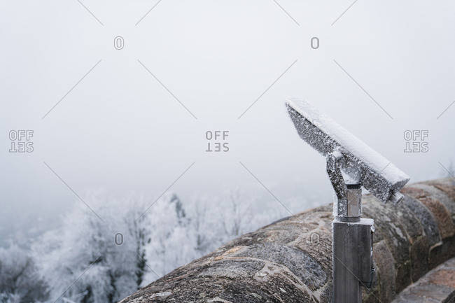 Old mono scope in hoar placed in winter coniferous garden on blurred background