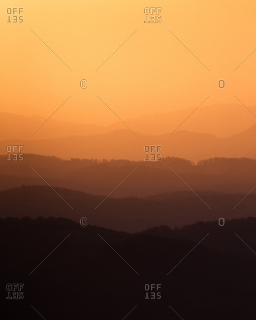 Beautiful view of amazing hilly terrain in orange light of setting sun