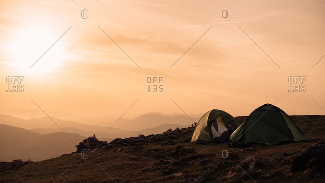 Anonymous people sitting near two camping tents on top of hill on background of majestic morning sky with rising sun