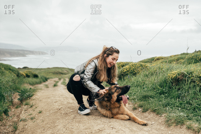 Young woman petting dog in nature