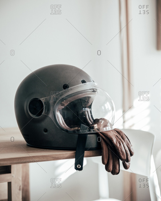 Close-up shot of motorcycle helmet and leather gloves lying on table in stylish room