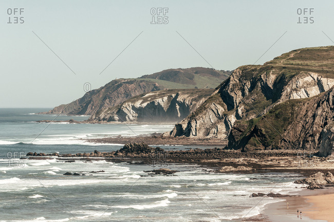 Magnificent view of amazing sea with rolling waves and rocky cliffs on background of gray sky