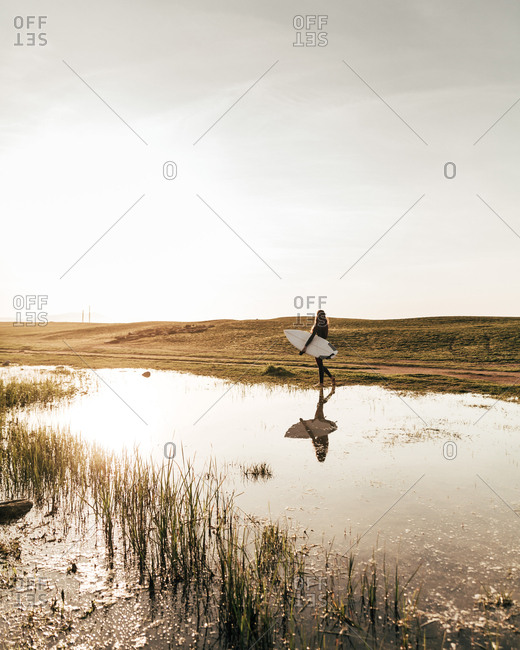 Side view of unrecognizable person carrying white surfboard while walking near pond in beautiful countryside
