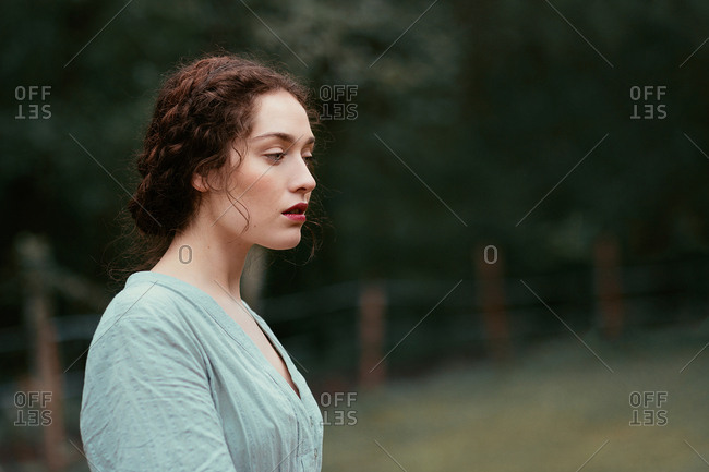 Side view of attractive young lady in elegant dress while standing on blurred background of beautiful countryside