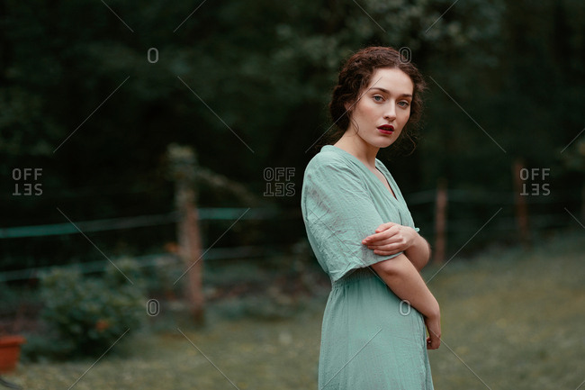 Side view of attractive young lady in elegant dress embracing herself and looking at camera while standing on blurred background of beautiful countryside