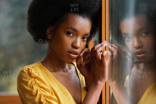 Side view of pretty African American female leaning on clean window glass
