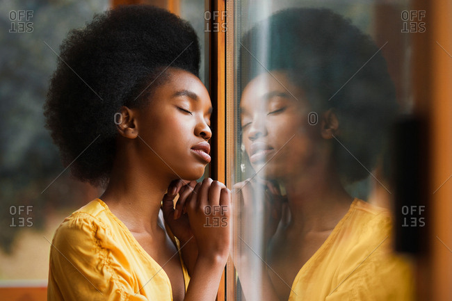 Side view of pretty African American female keeping eyes closed and leaning on clean window glass