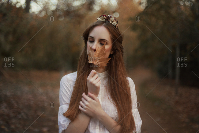 pretty young lady covering her face with leave standing on road of autumn forest