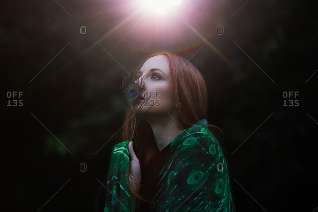 Side view of attractive young lady with ginger hair wearing peacock feathers patterned apparel while standing on blurred background of dark garden