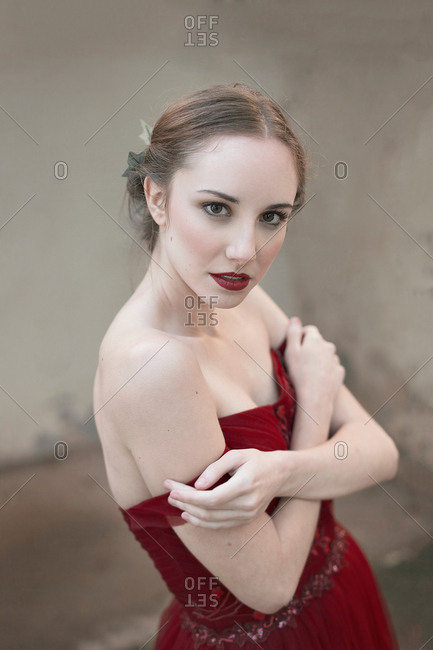 Side view of charming young woman in elegant evening dress embracing herself and looking at camera while standing