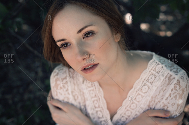 From above shot of pretty young lady in lace apparel embracing herself and looking away while standing on blurred background of nature