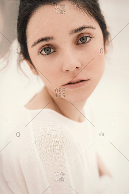 Side view of beautiful young female in casual outfit embracing herself and looking at camera while sitting on floor near glass railing in white room
